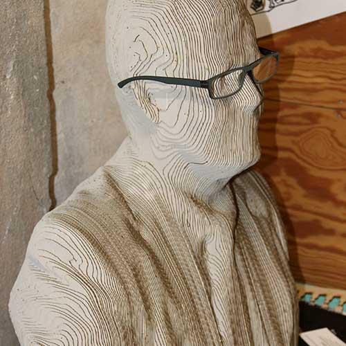 figur af mand lavet af sammenklistrede falde træstykker, der limet sammen ligner en mand.