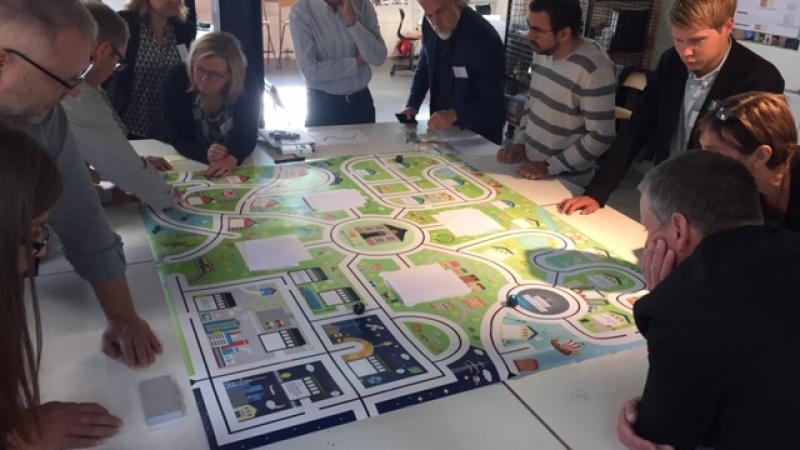 voksen der leger og studerer Ozobots på stor plakat med byer og veje.