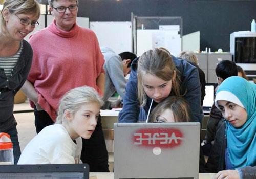 to voksne og fire piger er optaget af computerskærm