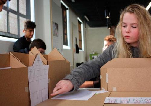 piger viser papmodel af et hus