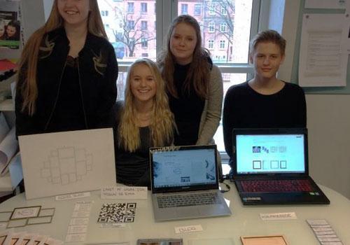 fire elever fremviser designtanker på et bord foran sig og på bærbare computerskærme