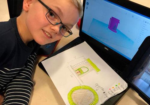 dreng viser glad tegning frem foran sin computer, hvor han er ved at bygge en model op