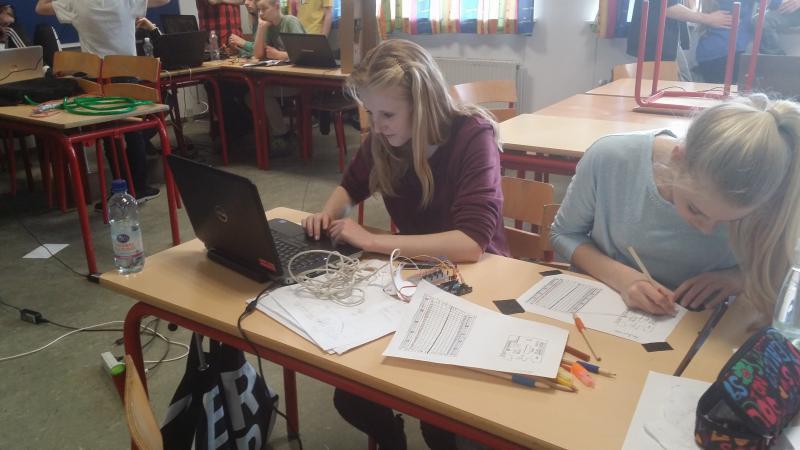 to piger i klasselokale koncentreret om at notere på papir og arbejde på bærbarcomputer