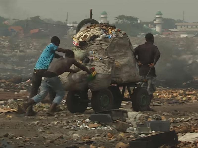 tre mænd har samlet et stort læs affald de skupper på, på losseplads