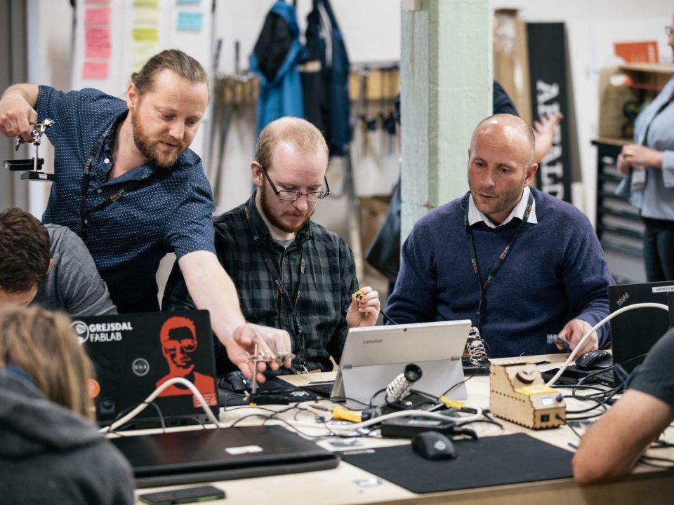 Mænd ved bord fuld af elektronik og bærbarer