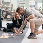en kvinde og mand på gulv, de eksperimenterer med en robot