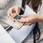 kvinde holder elektronsik genstand i hånden