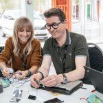 to voksne leger og eksperimenterer med elektronik. De sidder ved bord sammen med bærbarsomputer og holder elektronikken i hånden.
