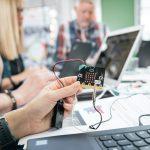 Voksne ved bærbarsomputer, holder elektronikken i hånden.