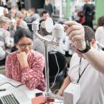 Voksne ved bærbarsomputer, holder elektronidk vejrmåler i hånden.