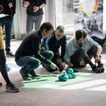 Tre voksne på gulv, der programerer små blå robotter sammensat af kugler