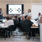Rum med mennesker hvor designmodel bliver forklaret