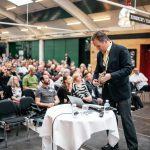 Foredragsholder og foredragssal fuld af mennesker