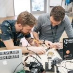 to mænd fordybet i at lodde et elektronisk kredsløb