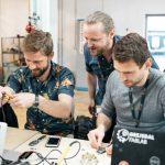 tre mænd ved bord og bærbarcomputer, prøver at konstruerer noget elektronisk