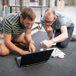 to mænd på knæ på gulvet, studerer intenst en skærm på en bærbarcomputer