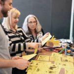 3 voksner studerer gule papirstykker med tegninger på