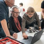 ung mand viser voksne hvordan de skal programmere en robot på computeren