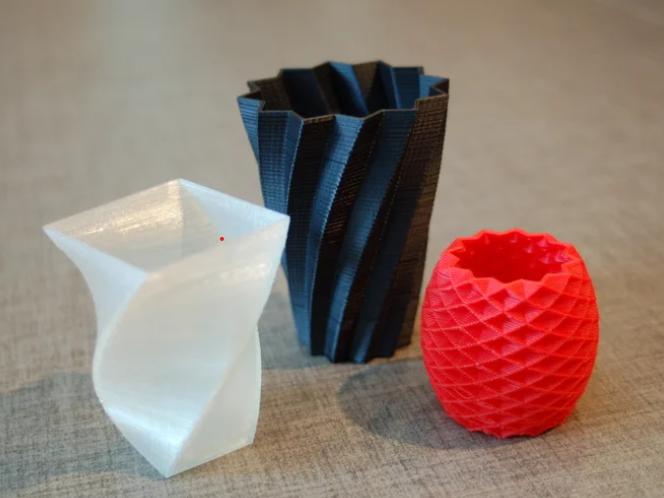 Tre 3Dprintede beholdere i rød, hvid og sort