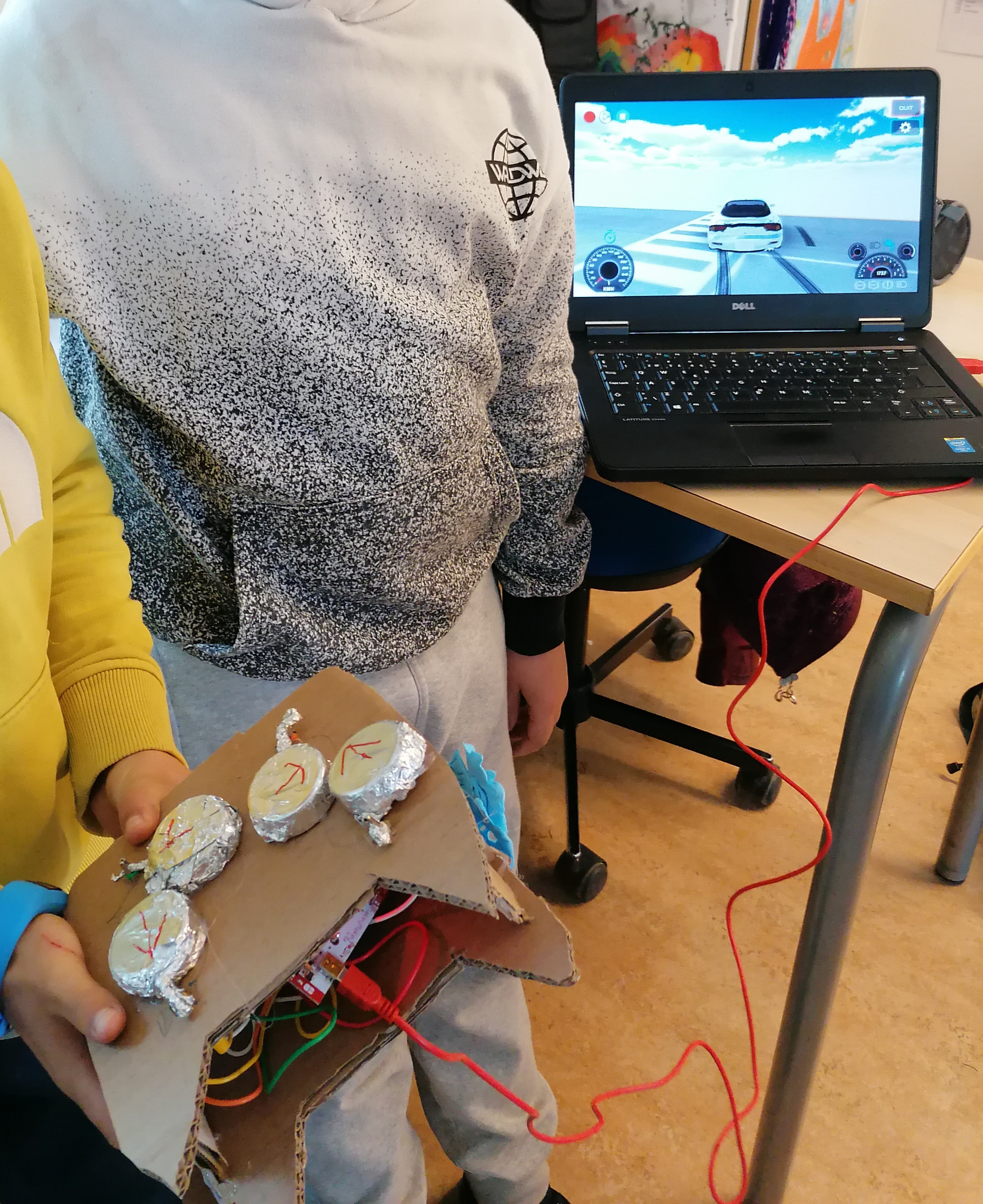 Elev viser controller lavet af pap med knapper af mælkelåg betrukket med stanniol