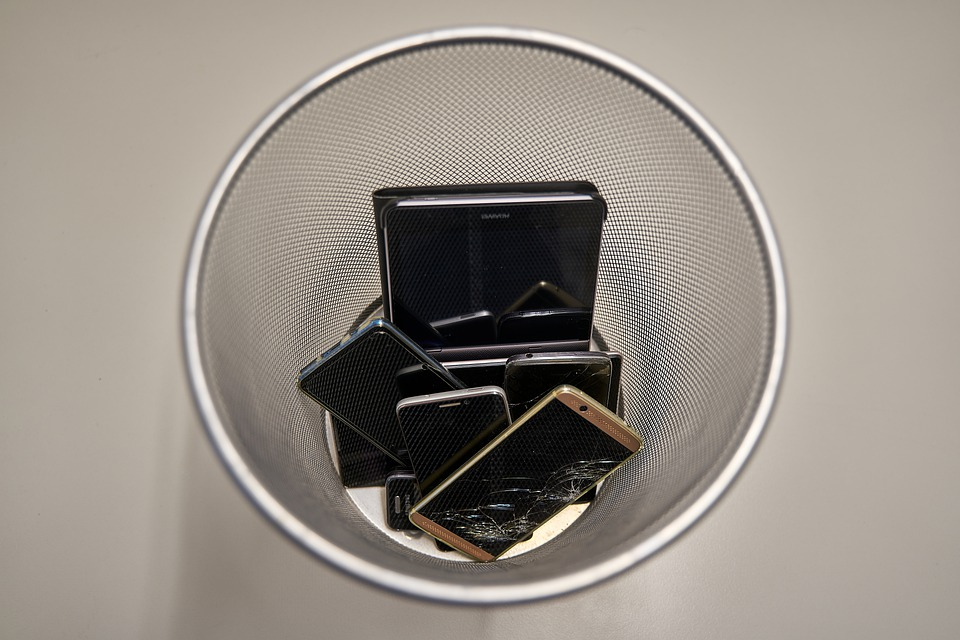 Gammel teknologi smidt i skraldespand som symbol på e-waste