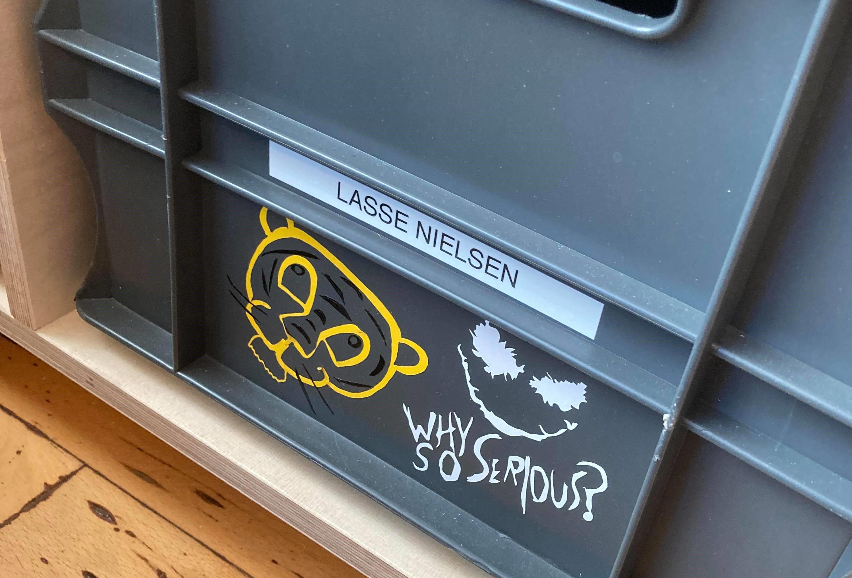 Grå plastik kasse med hvide og gule vinyl klistermærker, der personliggør kassen
