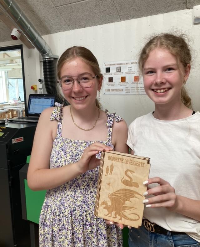 To piger viser et bogomslag, som de har lavet på laserskæreren i træfiner. Der er en drage på forsiden af bogen