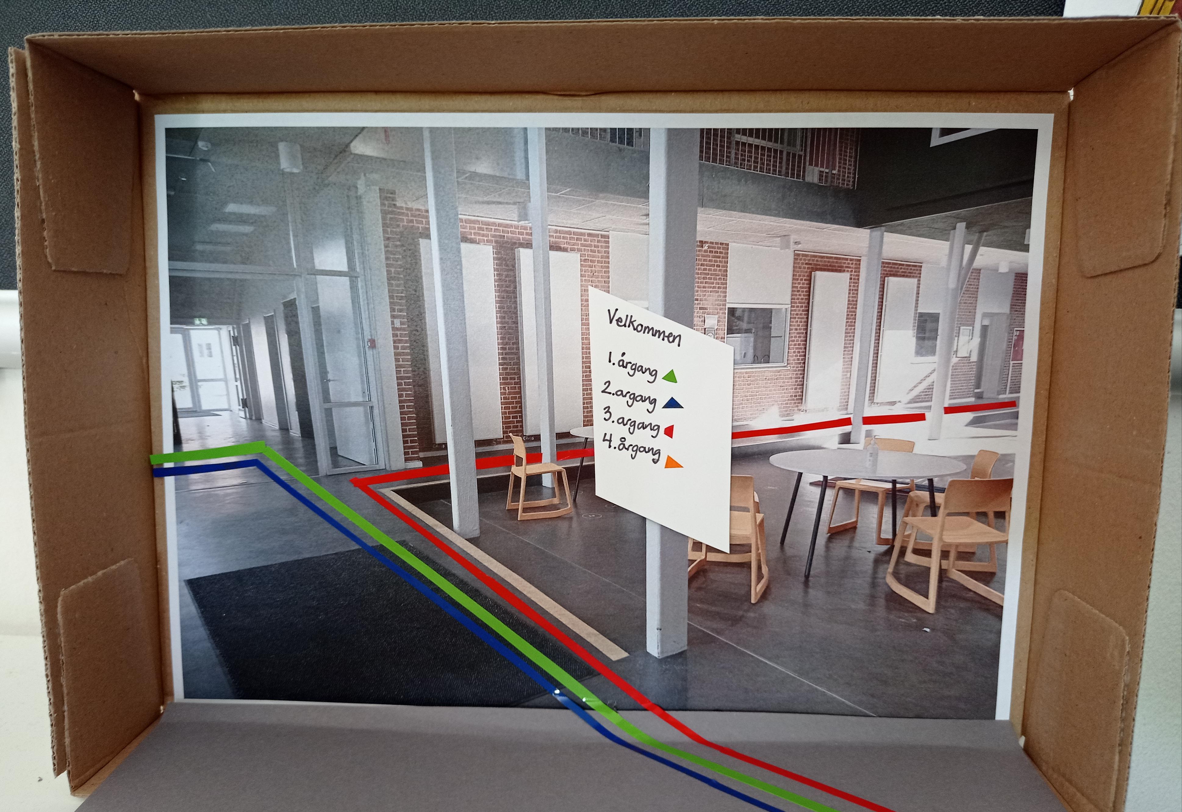 Et foto af et gangareal på en skole. Der er påsat et skilt og nogle farvede linjer på gulvet, så forskellige farvemarkeringer kan hjælpe børn og voksne med at finde rundt på skolen