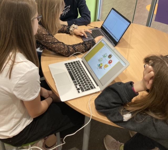 Fire elever arbejder i gruppe med med design af en bogforside
