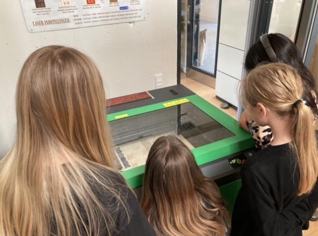 Fire elever står ved laserskærer og kigger gennem glaslåget på, at deres bogforside bliver skåret ud af skæreren
