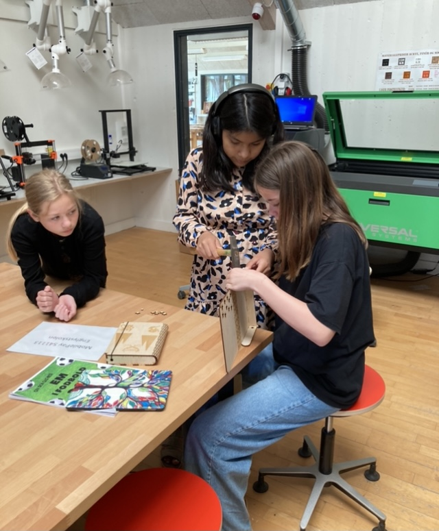 Tre elever sidder ved et bord og er ved forsigtigt at samle en bog, der er skåret ud på laserskærer. Den skal tappes sammen og de slår forsigtigt på tapperne for at få dem til at gå i hak
