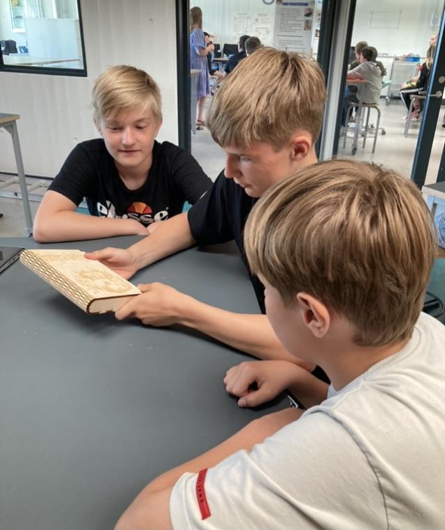 Tre elever sidder ved et bord og kigger på en bog, der er skåret på laserskærer. En af drengene har bogen i hånden