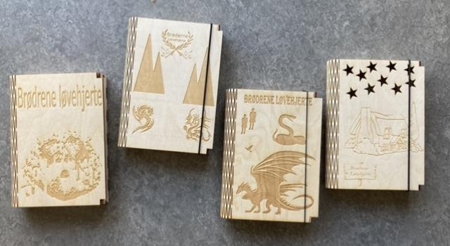 Fire forskellige eksempler på bøger, der er skåret på laserskærer og har graverede forsidebilleder