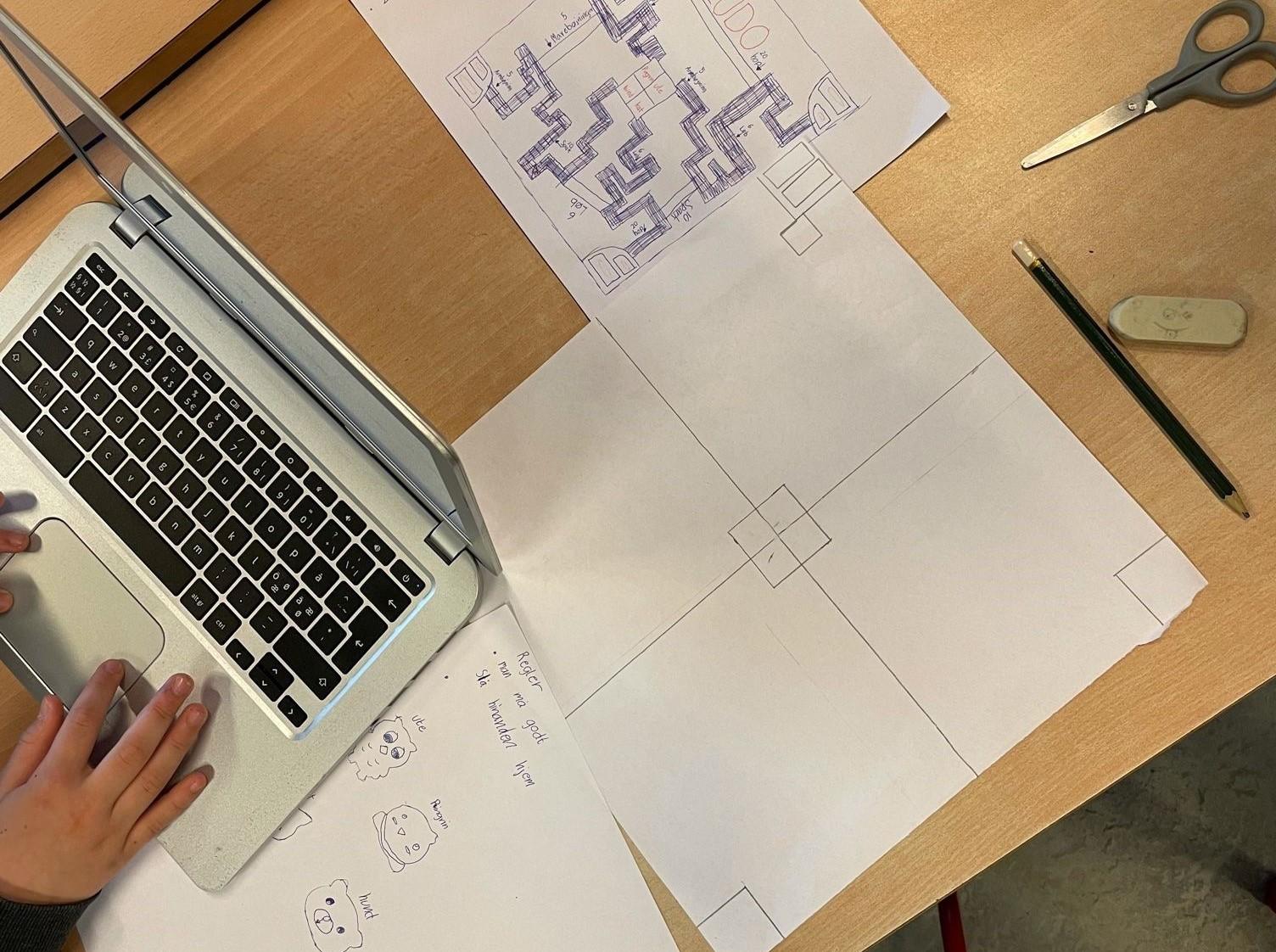 Elev arbejder ved computer; har skitser til design af eget spil liggende på bordet