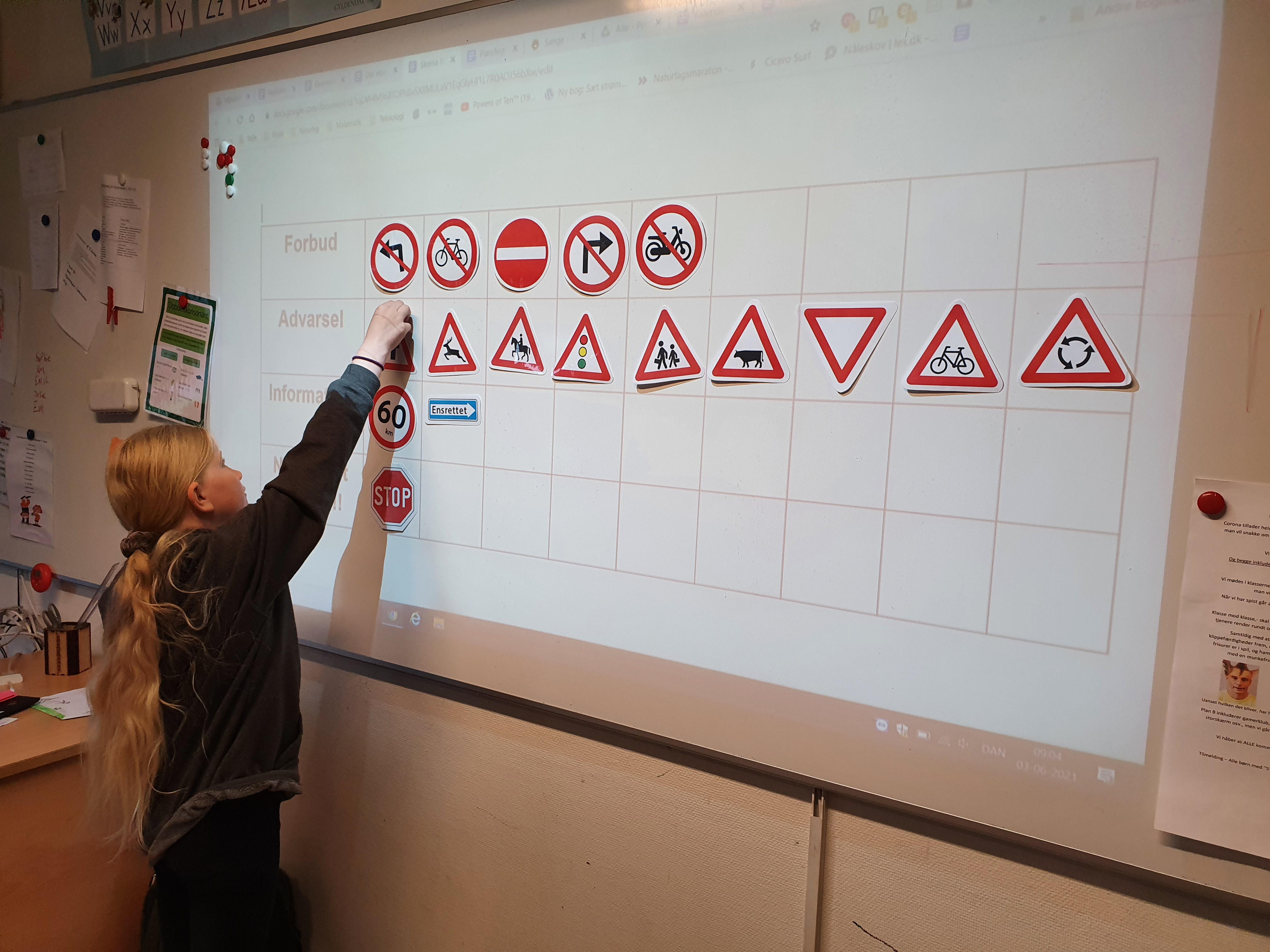 Elev er ved at placere et skilt i et skema på en tavle. Der er mange andre skilte i forskellige felter på tavlen