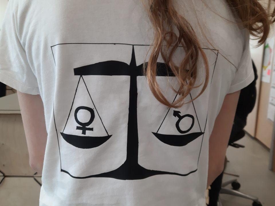 Elev med hvid t-shirt, hvorpå der er en sort vægt. I hver vægtskål er der placeret hhv. et mande- og et kvindetegn. Illustrationen er sort og lavet med vinyltryk. T-shirten er hvid