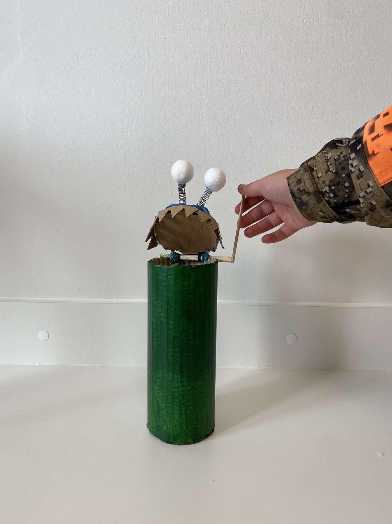 En elev har skabt en mockup i pap - af en skraldespand med tænder og øjne på låget.