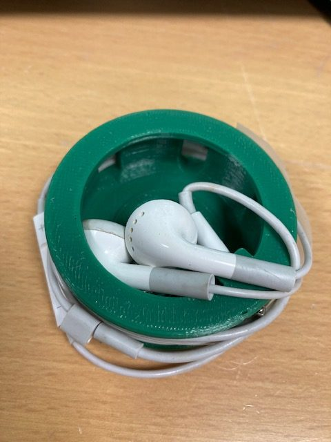 Små høretelefoner til en telefon i en lille grøn skål