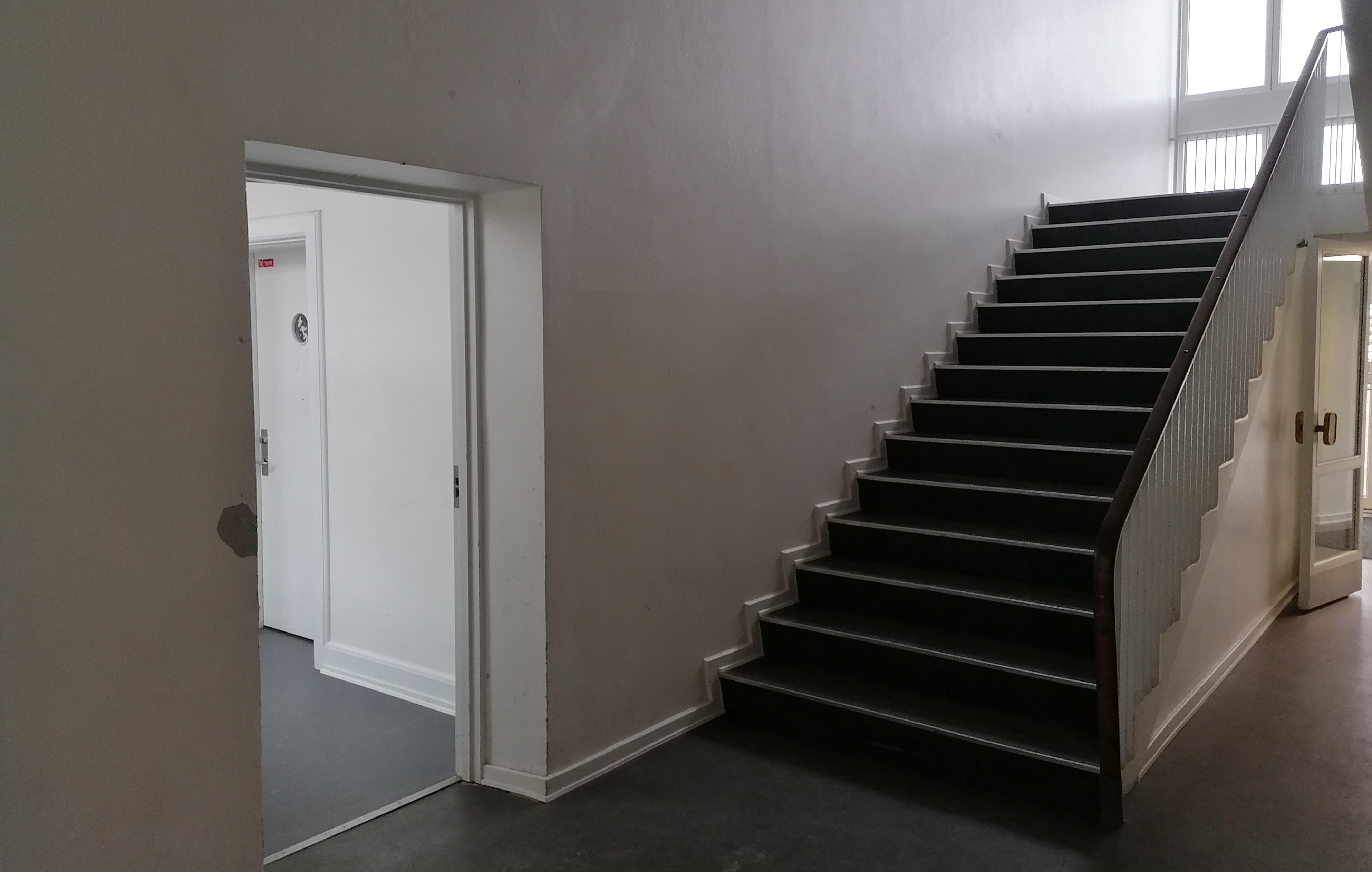 Gangareal på en skole - en dør går ind til et andet rum - en trappe fører et etage op
