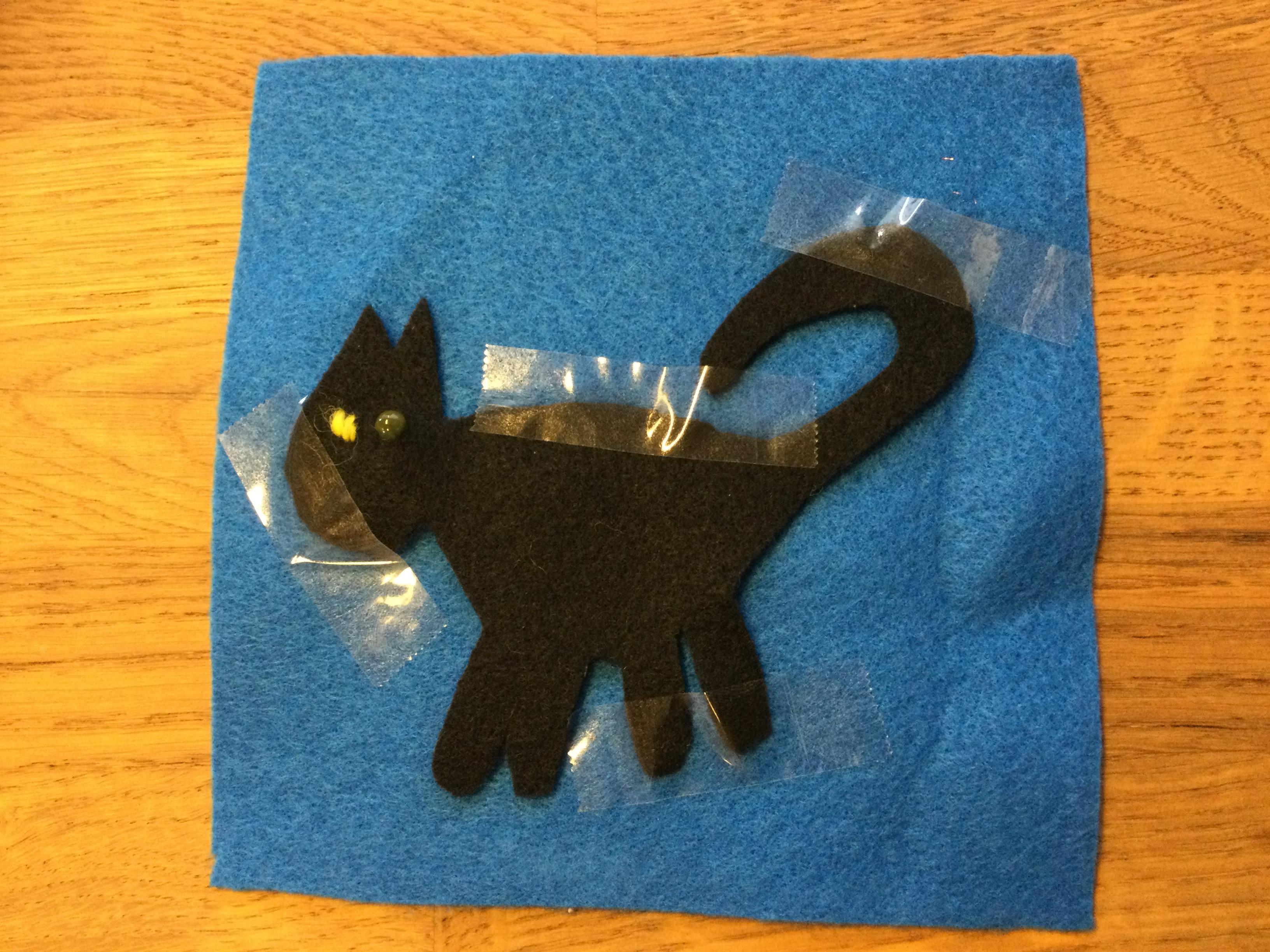Blå lomme med sort kat i filt