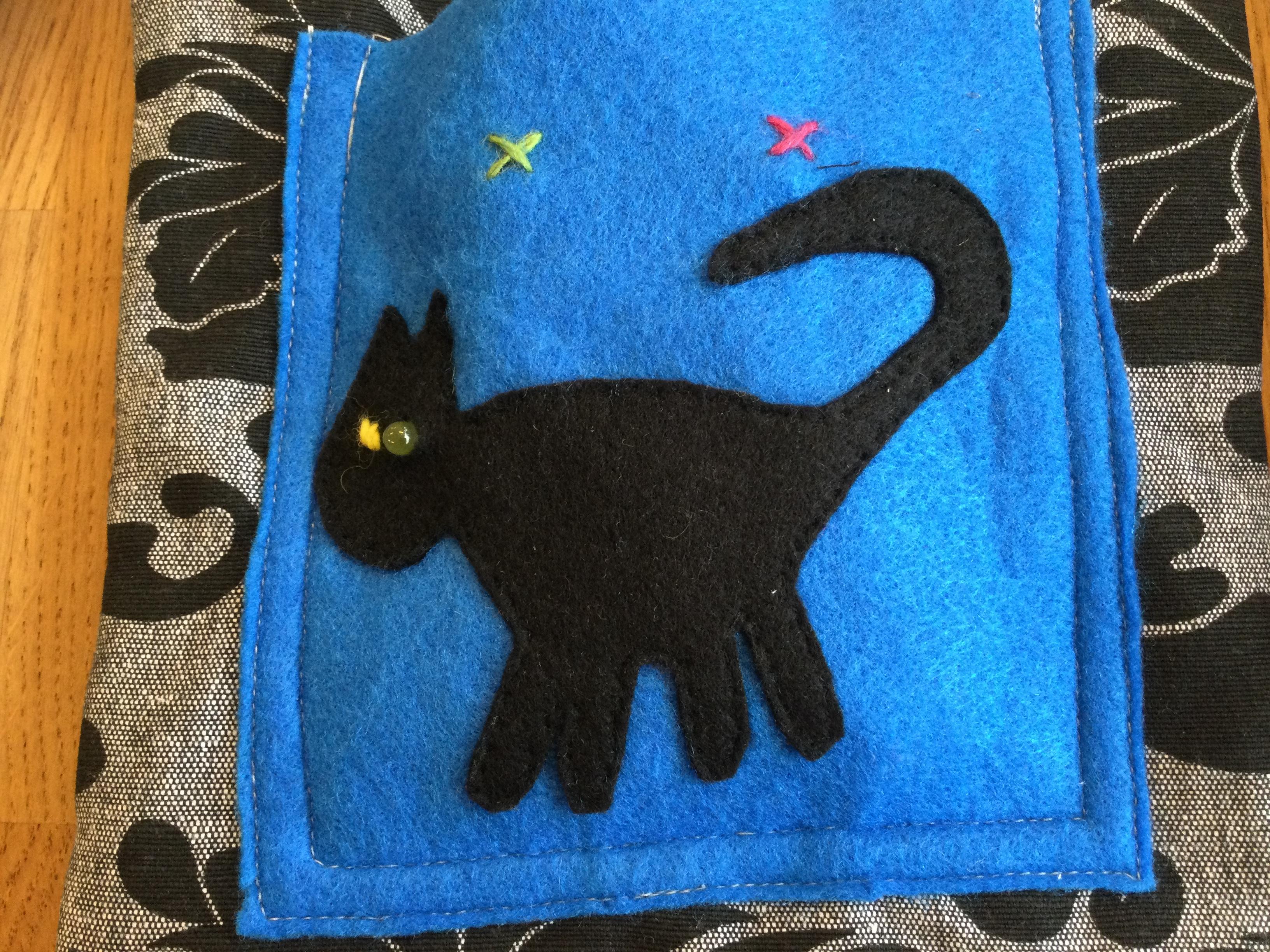 Taske med blå lomme med sort kat, der har dioder som øjne. Et grønt og et rødt kryds er syet og markerer, hvor der kan tændes og slukkes for dioderne