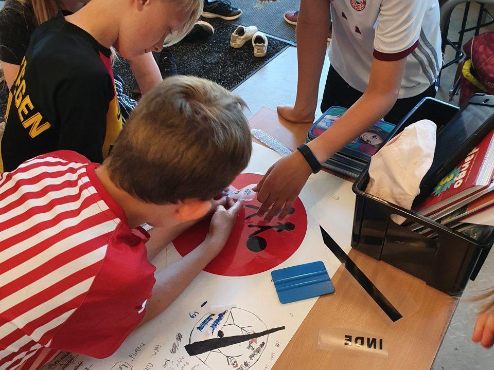 Elever samarbejder om at lave et skilt i vinyl. De har arbejdstegninger og skriveredskaber på bordet. De arbejder tæt og koncentreret