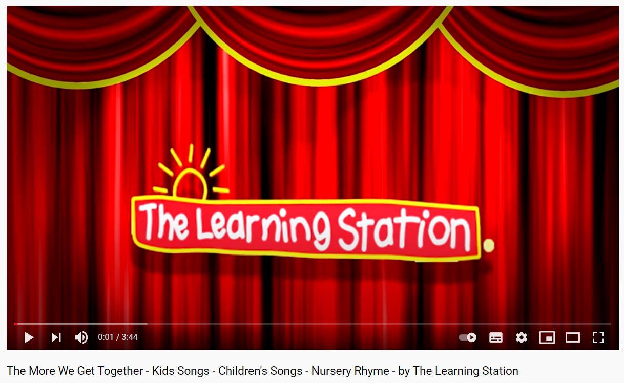 Skærmbillede fra musikvideoen The More We Get Togther. Det viser et rødt scenetæppe. Foran det er der et håndtegnet skilt, hvor der står The Learning Station