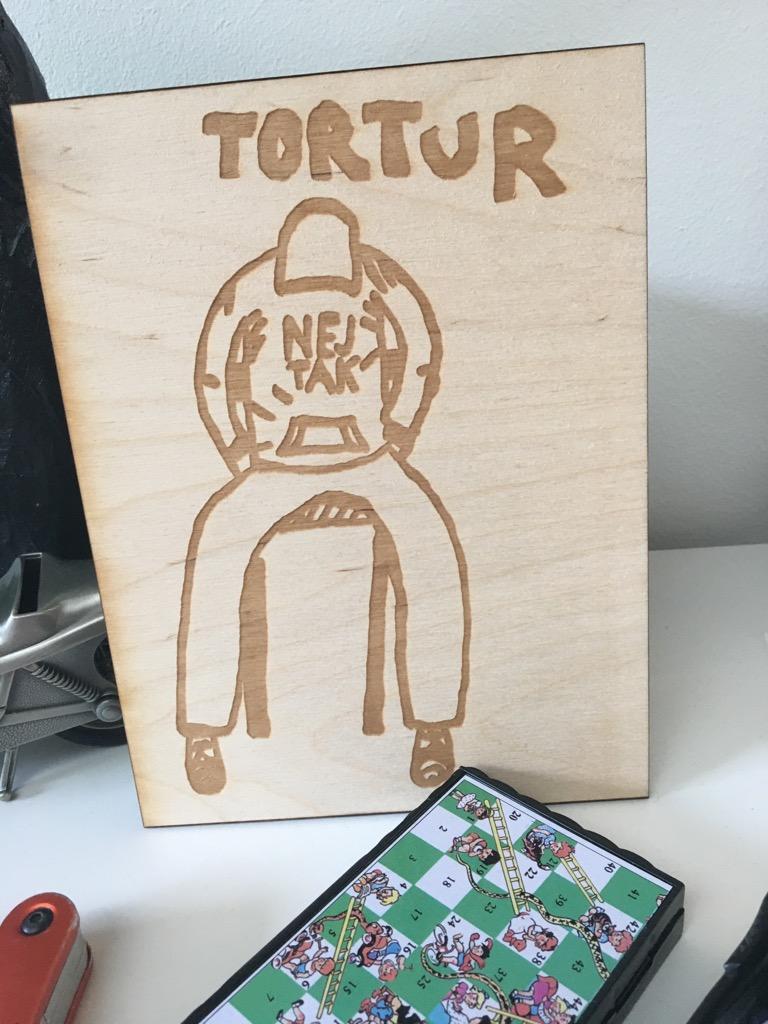 Skilt lavet i træ på laserskærer. Mand sidder på stol med foroverbøjet hoved. Tortur er skrevet som overskrift. På mandens trøje står der Nej Tak