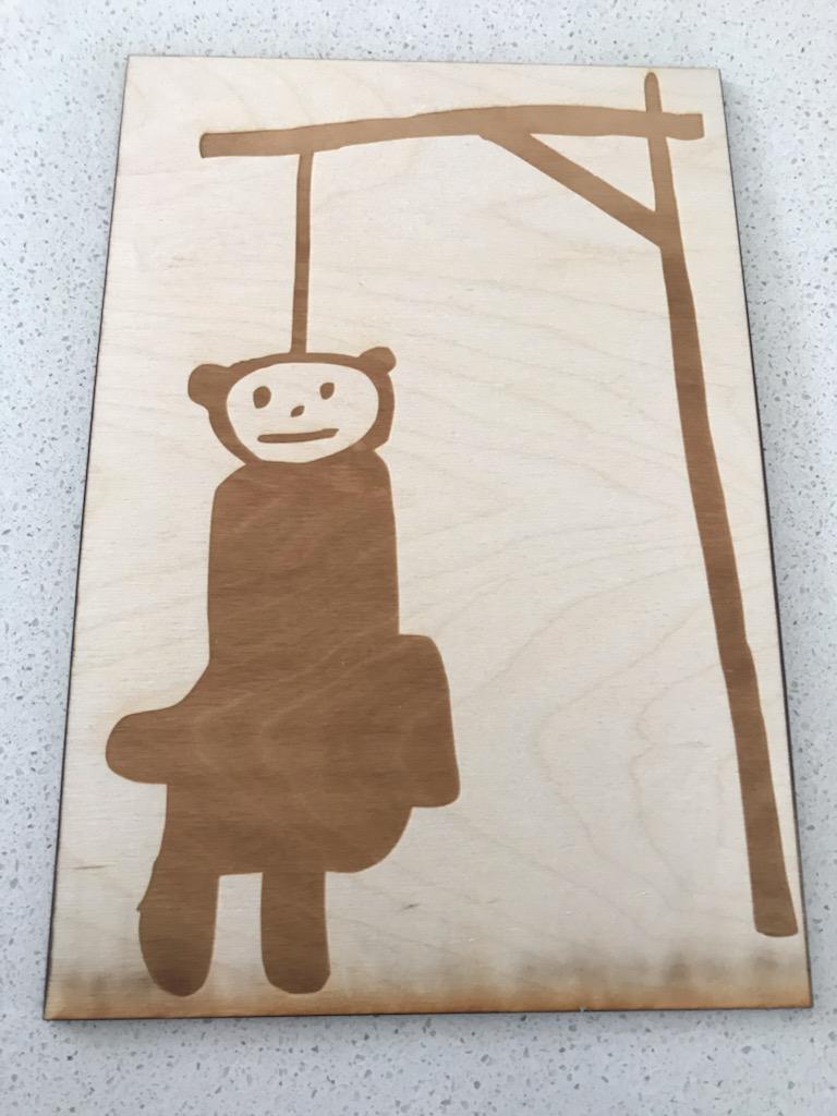 Skilt lavet i træ på laserskærer. Motivet er en bamse, som hænger i en galge
