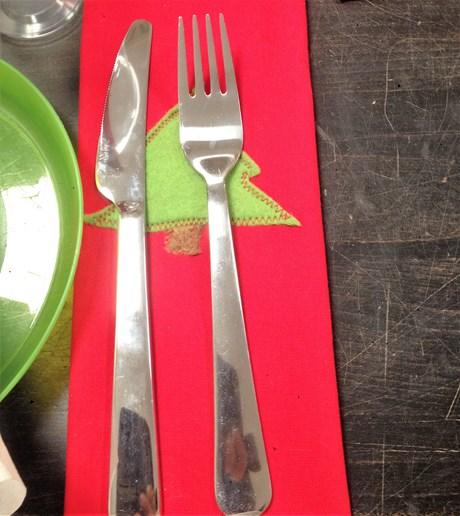 Del af bordopdækning: Kniv og gaffel ligger på en rød stofserviet, der er dekoreret med et grønt juletræ i filt