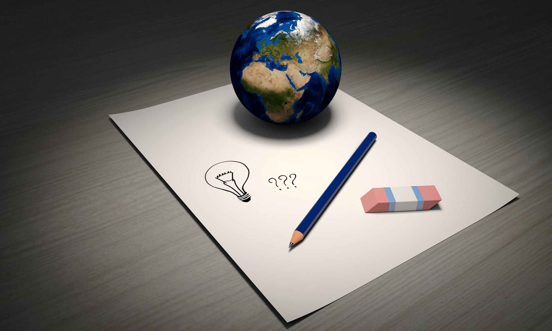 Papir på et bord - med en blyant, et viskelæder og en lille globus. På papiret er der tegnet en pære som symbol på at få ideer