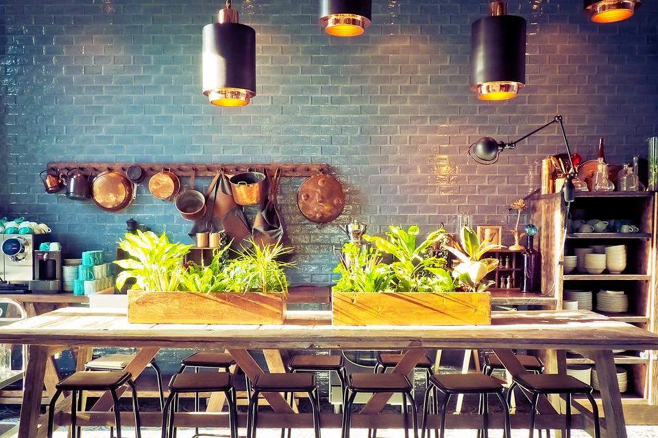 Køkken med bord med planter og lamper, der lyser ned på bordet