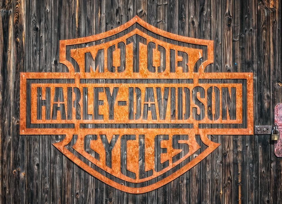 Harley Davidson logo i orange på rustik træbaggrund