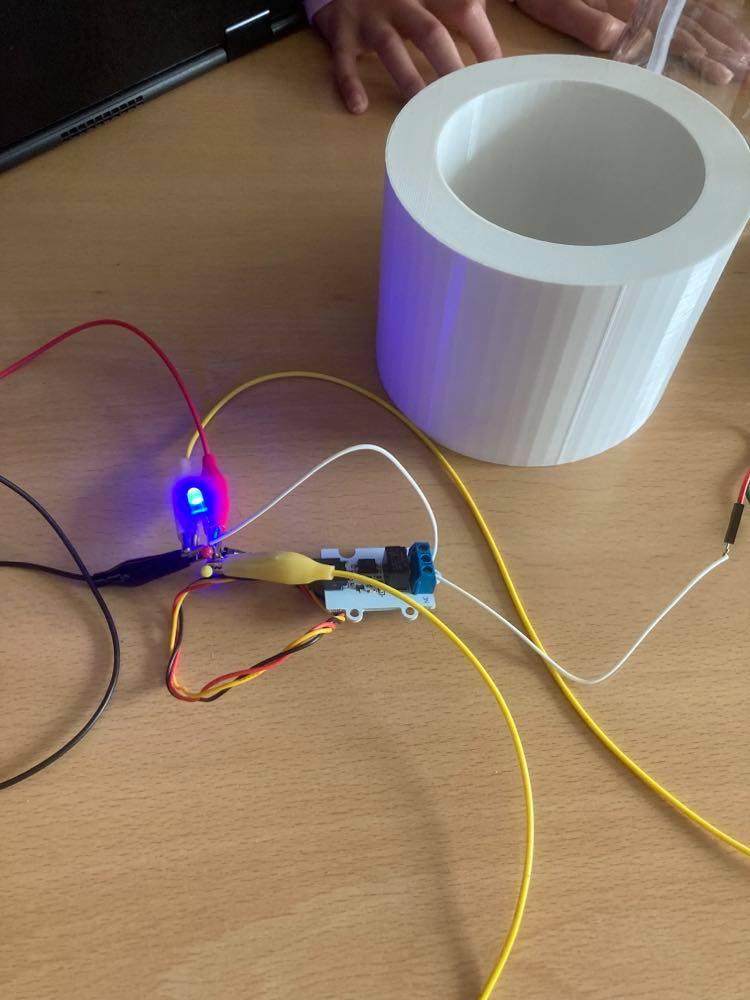 Krokodullenæb holder elektroniskkredsløb og en diode lyser blå.